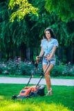 Pelouse de fauchage de femme dans le jardin arrière résidentiel Photo stock