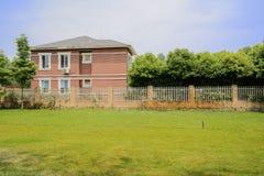 Pelouse herbeuse devant maison clôturée en été ensoleillé Photos libres de droits