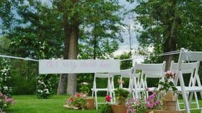 Pelouse verte avec des rangées des chaises en bois blanches Dans le premier plan le plat que notre histoire met en marche ici banque de vidéos