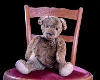Peluche antiga que senta-se em uma cadeira antiga Imagens de Stock Royalty Free