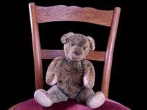Peluche antiga que senta-se em uma cadeira antiga Fotos de Stock Royalty Free