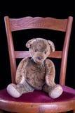 Peluche antiga que senta-se em uma cadeira antiga Fotos de Stock