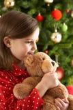 Peluche de afago da menina na frente da árvore de Natal fotografia de stock royalty free