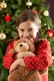 Peluche de afago da menina na frente da árvore de Natal foto de stock royalty free