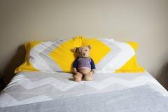 Peluche de mirada triste viejo en una cama matrimonial Foto de archivo