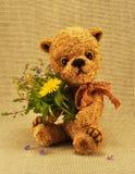 Peluche-lleve Misha con las flores Imagen de archivo
