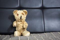 Peluche-urso velho do vintage que senta-se no sofá Imagem de Stock