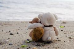 Peluches que abrazan en la playa Foto de archivo libre de regalías