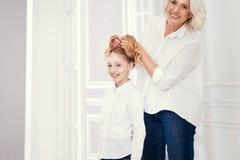 Peluquería cuidadosa su nieta del preadolescente en casa Fotografía de archivo