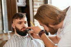 Peluquería de caballeros El hombre consigue el pelo de la barba para cortar imagenes de archivo