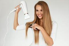 peluquería Mujer que seca el pelo recto largo sano hermoso fotos de archivo