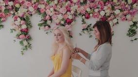 Peluquería profesional haciendo peinado a una chica en el estudio almacen de video