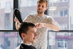 Peluquería profesional Tirado de un cabello seco del peluquero con el secador del soplo del cliente del hombre fotografía de archivo