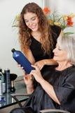 Peluquero Advising Hair Color al cliente Foto de archivo