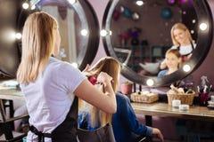 Peluquero agradable que peina el pelo de su cliente Fotos de archivo libres de regalías