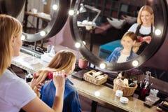 Peluquero agradable que toma el cuidado del pelo de las muchachas Fotografía de archivo libre de regalías