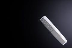 Peluquero blanco del peine en fondo negro Concepto del salón del peluquero Foto de archivo