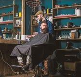 Peluquero con el recorte acabado de las podadoras de pelo a disposición Cliente del inconformista que consigue corte de pelo El p imagen de archivo