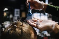 Peluquero con un cepillo para aplicar el tinte de pelo El colorear en la peluquería de caballeros imagenes de archivo