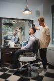 Peluquero con un cepillo para el pelo que trabaja en un nuevo corte de pelo para un cliente Cliente barbudo en el fondo de la bar Fotografía de archivo libre de regalías