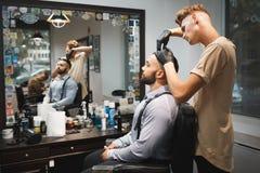 Peluquero con un cepillo para el pelo que trabaja en un nuevo corte de pelo para un cliente Cliente barbudo en el fondo de la bar Foto de archivo