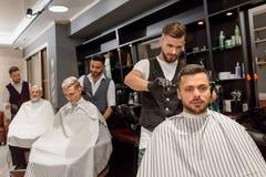 Peluquero concentrado que hace corte de pelo profesional y elegante al cliente fotos de archivo