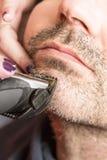 Peluquero, cortando la barba en su lugar de trabajo Imágenes de archivo libres de regalías