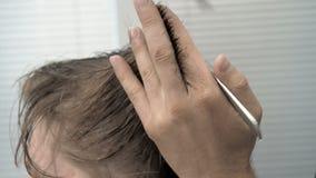 Peluquero Cuts Hair en el templo y nuca al cliente en un salón Hombre que se sienta en butaca de los peluqueros mientras que esqu metrajes
