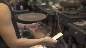 Peluquero de los niños que usa el peine y las tijeras para el corte de pelo del niño pequeño en salón de la peluquería Peinado de almacen de video