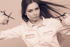 Peluquero de sexo femenino con las tijeras de los condensadores de ajuste Imágenes de archivo libres de regalías