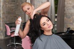 Peluquero de sexo femenino joven que aplica el espray en el pelo del cliente foto de archivo libre de regalías