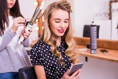 Peluquero de sexo femenino que aplica a la enderezadora del pelo para el pelo largo de la mujer joven sonriente Imágenes de archivo libres de regalías