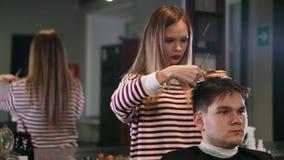 Peluquero de sexo femenino que corta el pelo del cliente sonriente del hombre en el salón de belleza almacen de metraje de vídeo