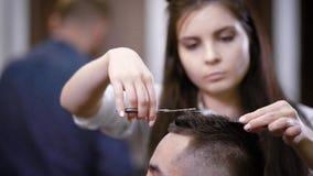 Peluquero de sexo femenino que hace corte de pelo con las tijeras y el peine Cliente masculino que se sienta en la silla Foco sel almacen de metraje de vídeo