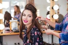 Peluquero de sexo femenino que hace el peinado a la mujer linda en salón de belleza Fotografía de archivo