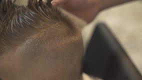 Peluquero de sexo masculino que usa la maquinilla de afeitar eléctrica para el peinado de los niños Peluquería del rato del niño  almacen de metraje de vídeo