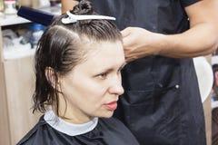 Peluquero del estilista en la peluquería de caballeros que hace el primer del corte de pelo foto de archivo libre de regalías