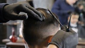 Peluquero en los guantes negros que peinan el pelo de un niño asiático y que se preparan para cortarlos 60 fps