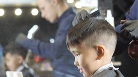 Peluquero en los guantes negros que rocían y que peinan el pelo de los fps asiáticos de un niño 60