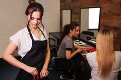 Peluquero hermoso de la mujer con el delantal negro que toma a pelo el clip profesional antes de hairstyling en fondo del salón fotos de archivo