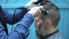 Peluquero hermoso de la mujer que hace el corte de pelo masculino con la maquinilla de afeitar eléctrica del pelo en salón de la  metrajes