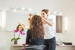 Peluquero joven hermoso que da un nuevo corte de pelo al cliente femenino en la sala Imágenes de archivo libres de regalías