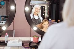 Peluquero mayor que trenza su pelo adolescente de los clientes Fotografía de archivo libre de regalías