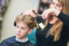 Peluquero o estilista en el trabajo pelo femenino del niño del corte del peluquero Imagenes de archivo