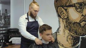 Peluquero para los hombres barbershop Un individuo joven consigue un servicio del corte de pelo y del cuidado del cabello de un h almacen de metraje de vídeo