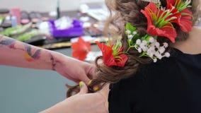 Peluquero, peluquero que acaba el peinado creativo con las flores para la muchacha adolescente metrajes