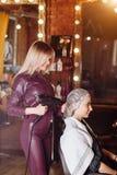 Peluquero profesional agradable sonriente que trabaja con el cliente femenino que sostiene el secador de pelo profesional en pelu imagen de archivo libre de regalías