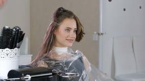 Peluquero profesional, estilista que colorea el pelo adolescente de la muchacha almacen de video