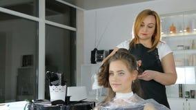Peluquero profesional, estilista que colorea el pelo adolescente de la muchacha almacen de metraje de vídeo