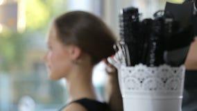 Peluquero profesional, estilista que prepara el peinado para la muchacha adolescente que usa el pasador para el pelo de fijación almacen de video